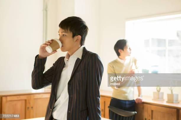 Young men drinking coffee in room