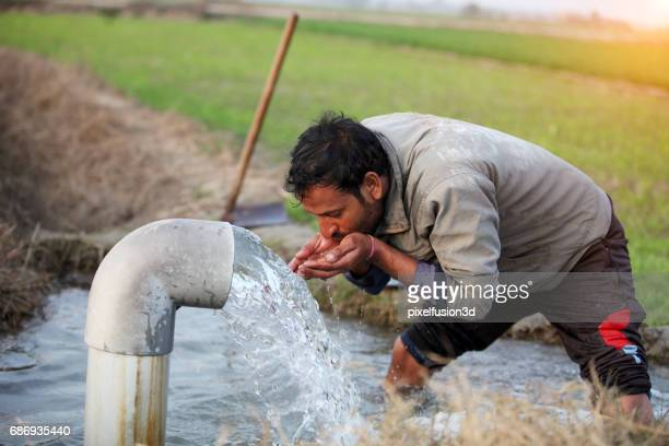 young men drinking outdoor in the field - water conservation stock pictures, royalty-free photos & images