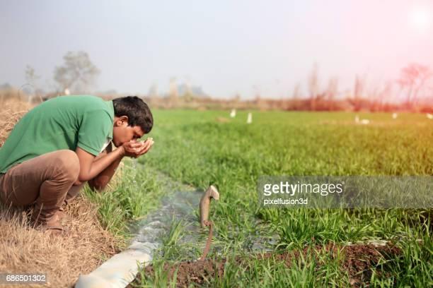 Junge Männer Trinkwasser in der Nähe von grünen Wiese