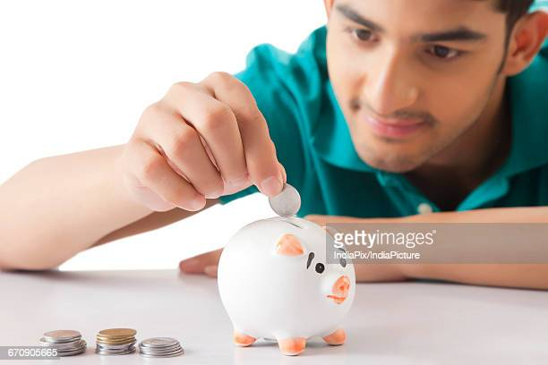Young men dropping a coin in the piggy bank