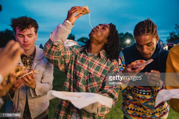 Young Men Eating Pizza at Festival