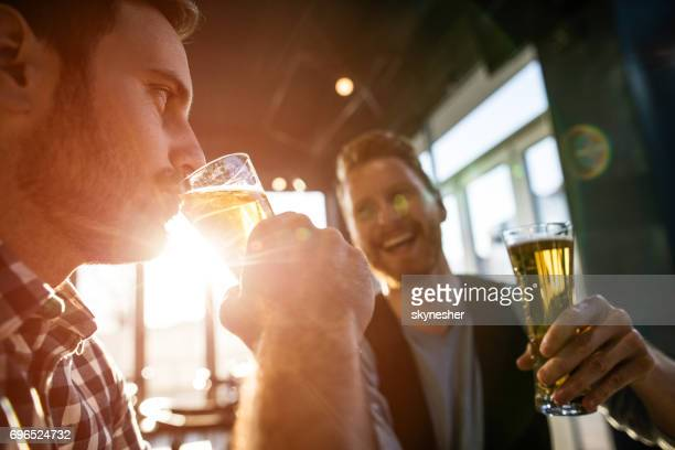 Young men enjoying in a beer at the bar.