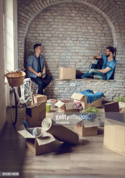 Young men enjoying in coffee break while moving into their new apartment.