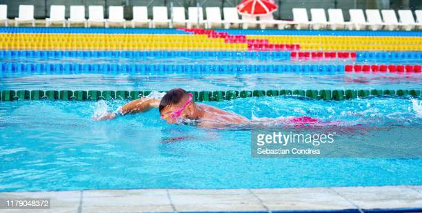 young men excercise in the swimming pool to win. - length stock pictures, royalty-free photos & images