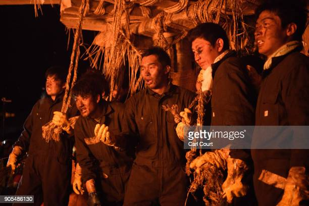 Young men from Nozawaonsen village who are tasked with protecting the wooden shrine pause between attacks by people trying to set fire to it during...