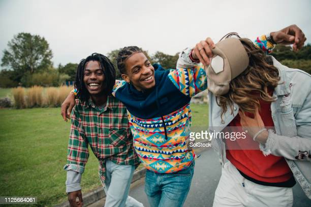 young men hanging out in the park - graduation crowd stock pictures, royalty-free photos & images