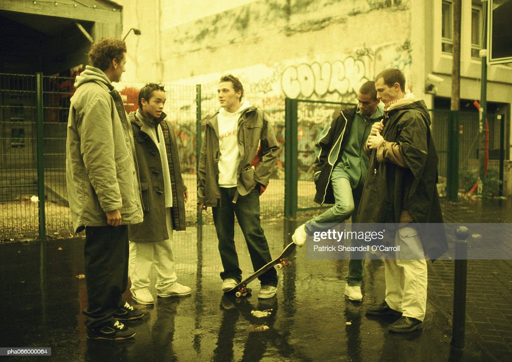 Young men hanging out together on street corner, wall with grafitti in background : Stockfoto