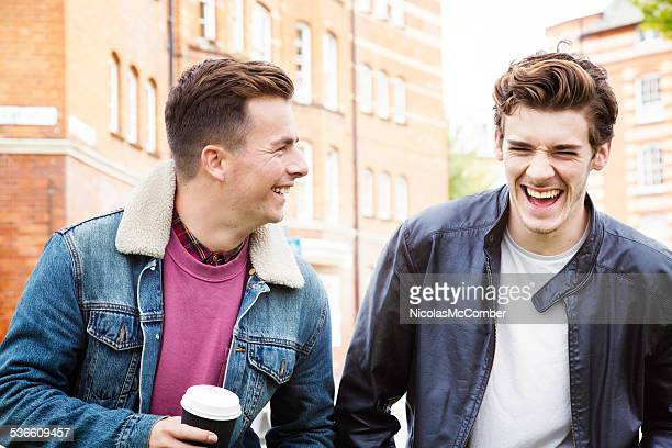 Young men having a good laugh while commuting on foot