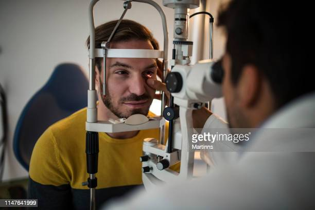 young men having an eye exam at ophthalmologist's office. - eye test equipment stock pictures, royalty-free photos & images