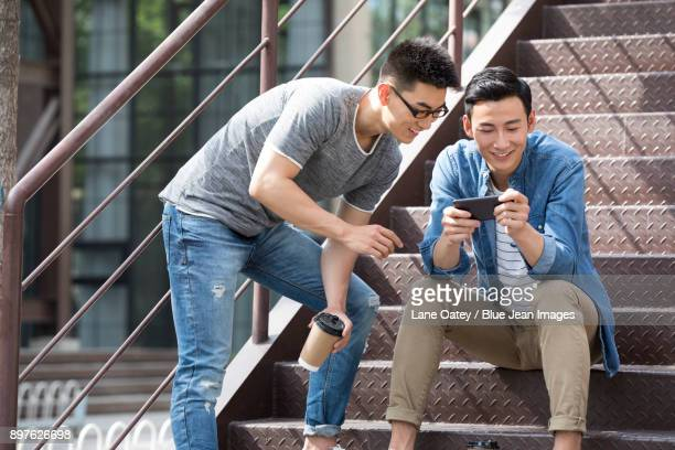 young men having coffee break outdoors - handheld video game stock pictures, royalty-free photos & images