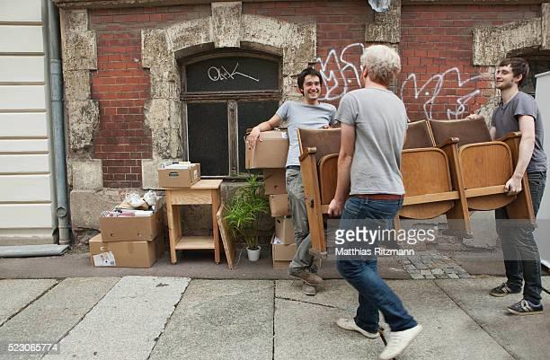 young men helping a friend move - porter photos et images de collection
