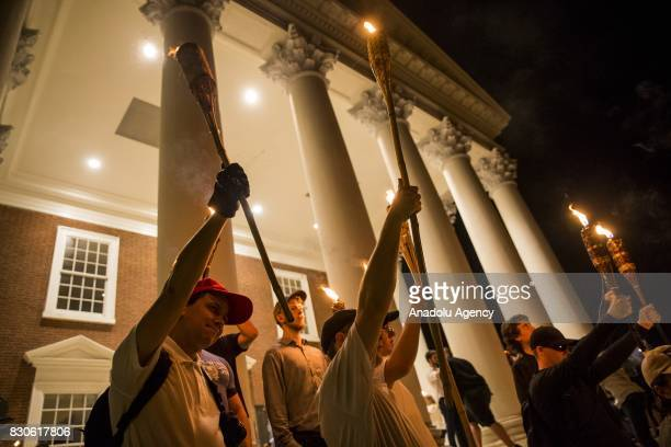 Young men hold up torches on the steps of the Rotunda as other Neo Nazis AltRight and White Supremacists march through the University of Virginia...