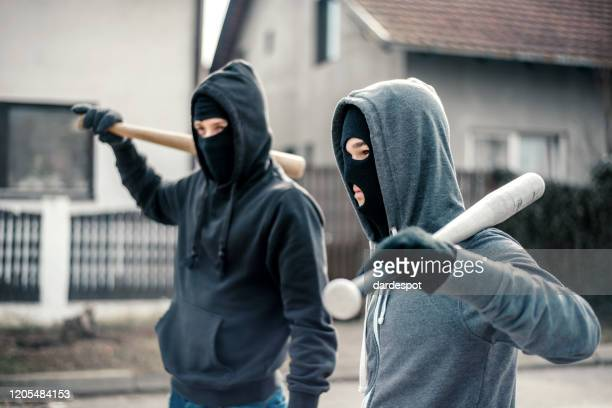young men holding a baseball bat symbolizing crime - looting stock pictures, royalty-free photos & images