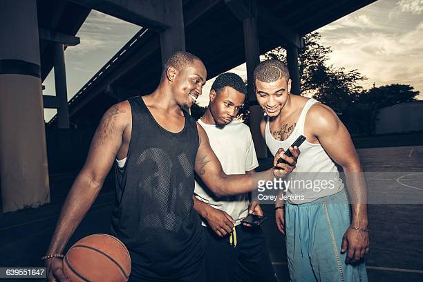 Young men holding basketball looking at smartphone smiling