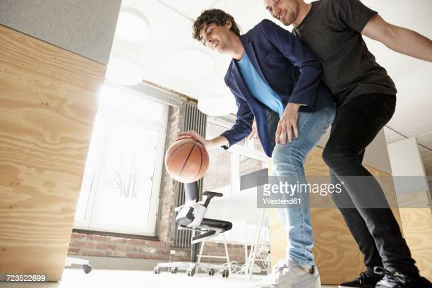 Young men in office playing basketball