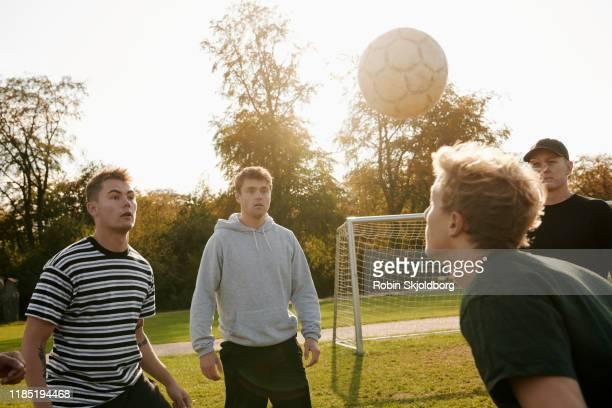 young men in park juggling with football - fußball freundschaftsspiel stock-fotos und bilder