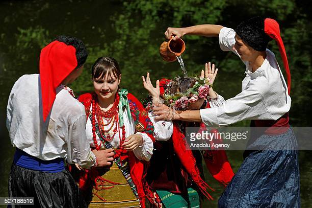 Young men in Ukrainian traditional clothes pour water on the women during folk Easter Tradition of pouring water called 'Pouring Monday' in open air...