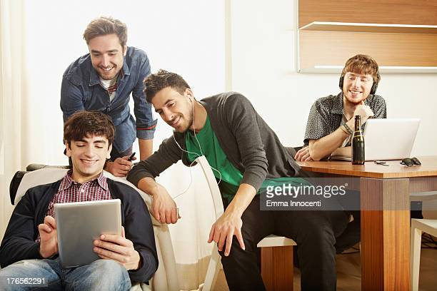 Young men indoors looking at computer and tablets
