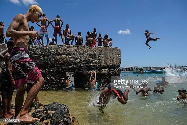 Young men jump into the sea at Boa Viagem beach in Salvador Bahía Brazil on January 1 2015 AFP PHOTO / YASUYOSHI CHIBA