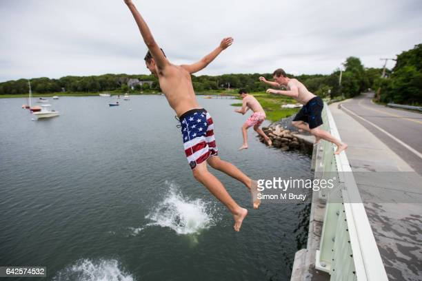 Young men jump of a bridge in the North Falmouth area on July 18 2015 in Meganestt Beach Cape Cod Massachusetts Cape Cod hosts the collegiate summer...