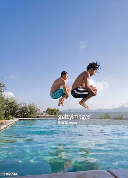 Young men jumping into a pool