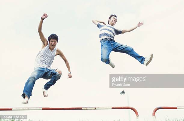 Young men jumping, low angle view