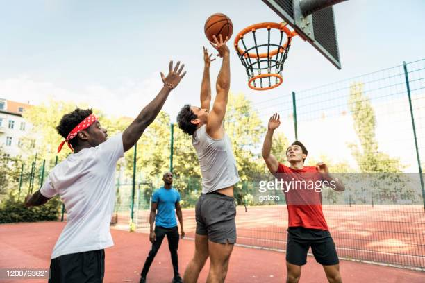 young men jumping with basketball on hardcourt - making a basket scoring stock pictures, royalty-free photos & images