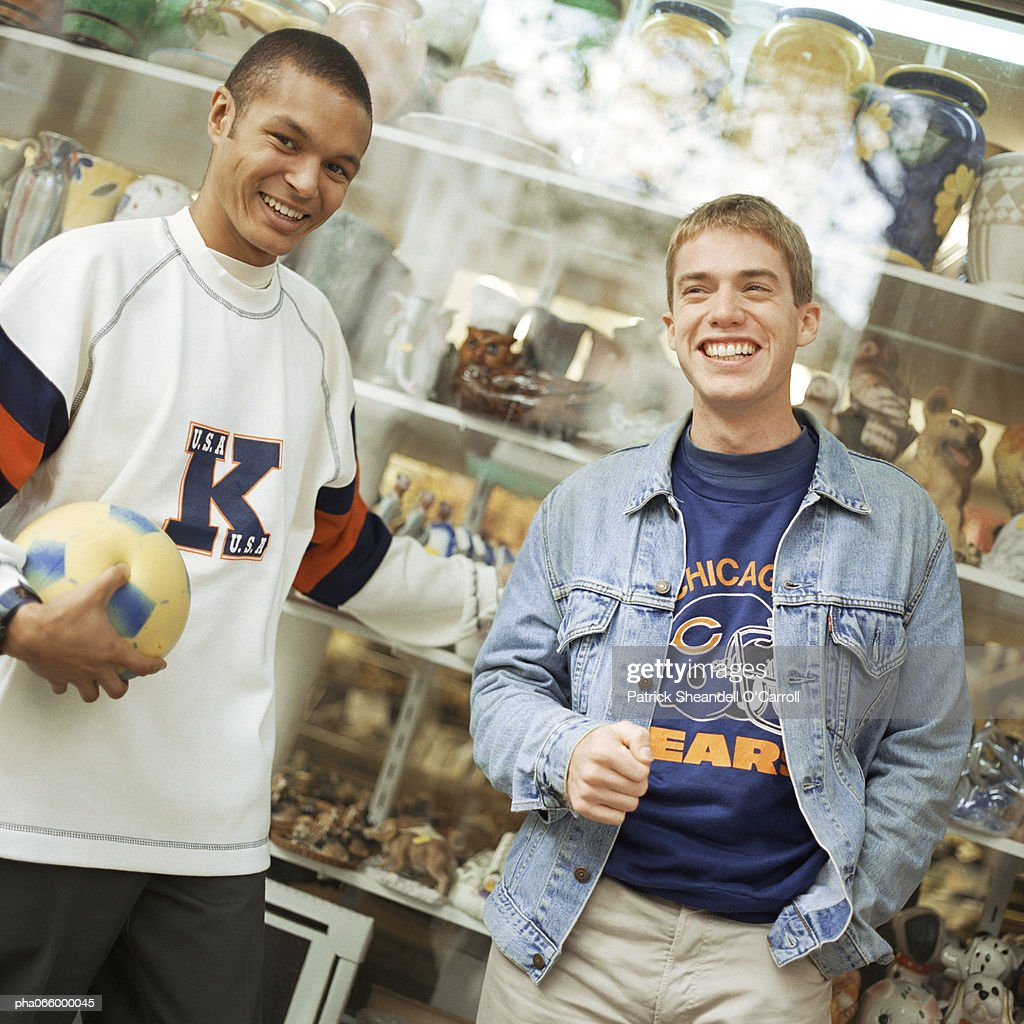 Young men leaning against store window, smiling, facing camera. : Stockfoto
