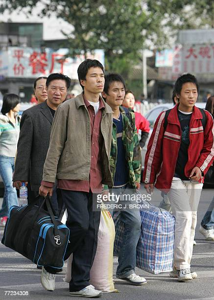 Young men migrant workers among China's rural millions who leave the countryside for work in the cities return to Beijing 09 October 2007 after the...