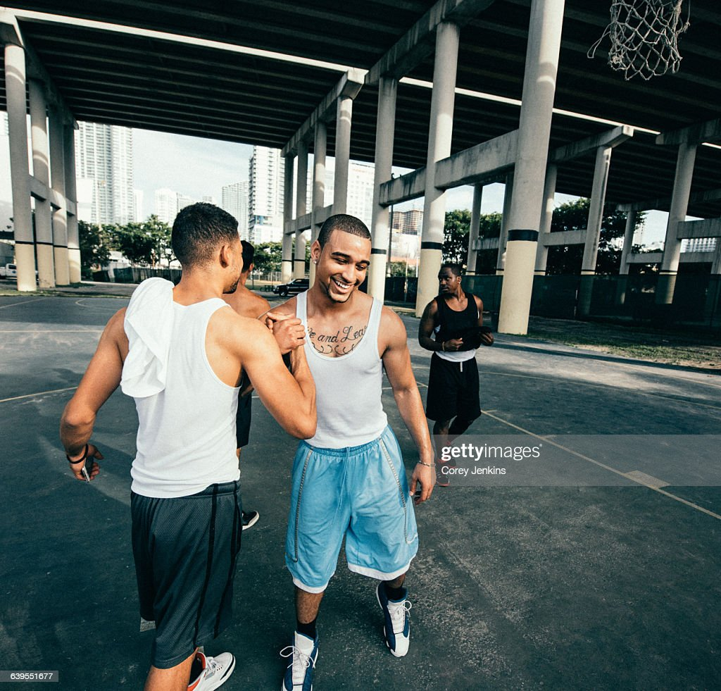 Young men on basketball court connecting with handshake after basketball game smiling : Stock Photo
