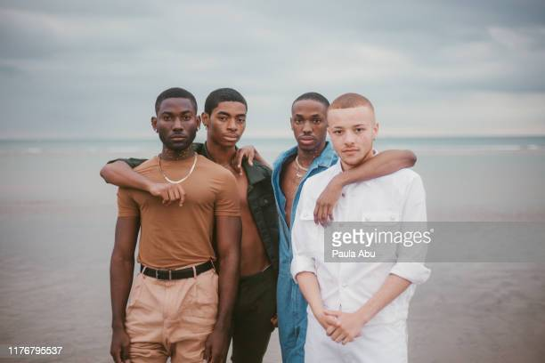 young men on beach - lgbtq stock pictures, royalty-free photos & images