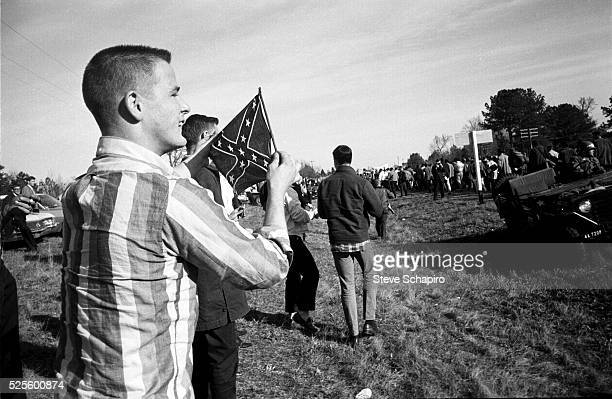 Young men one holding a Southern Confederate flag heckle marchers during the third SelmaMontgomery March