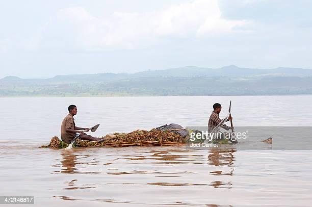 Young men paddling reed boat on Lake Tana