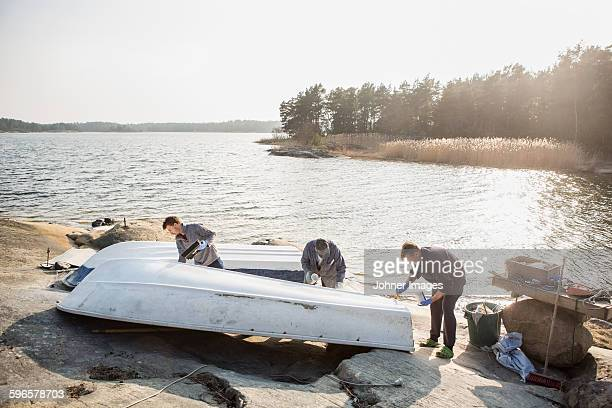Young men painting boat
