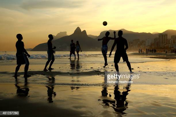 Young men play beach football as the sunsets on Ipanema beach on June 25 2014 in Rio de Janeiro Brazil