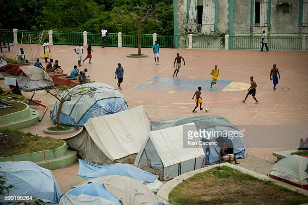 Young men play soccer at a tent camp in Place Toussaint Louverture named for one of the heroes of the revolution in Jacmel Haiti April 2 2011