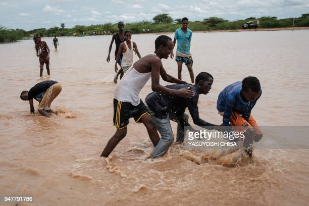 Young men play with a ball in floodwaters after a heavy rainy season downpour as they seek to fill sandbags at the Dadaab refugee complex, in the...