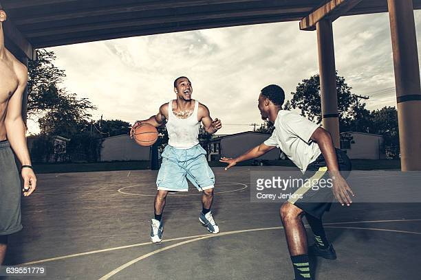 Young men playing basket ball on basket ball court smiling