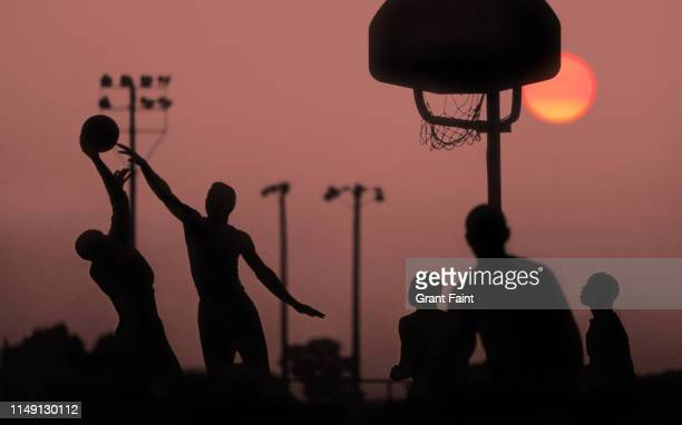 young men playing basketball at sunset. - sport venue stock pictures, royalty-free photos & images