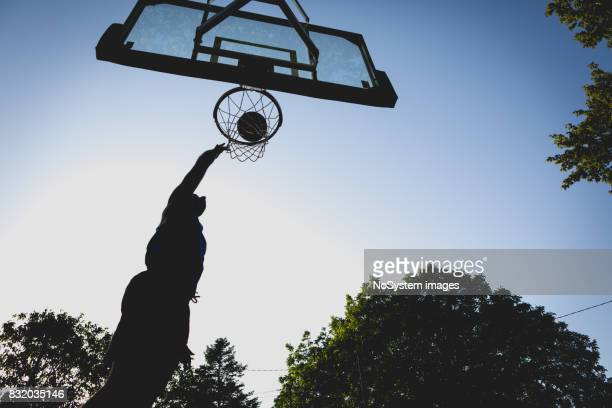 young men playing basketball on outdoor court - traditional sport stock photos and pictures