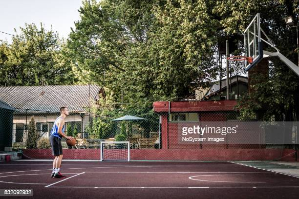 young men playing basketball on outdoor court - shooting baskets stock pictures, royalty-free photos & images