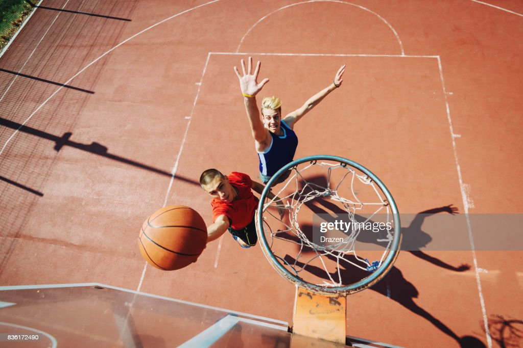 Young men playing basketball one on one : Stock Photo
