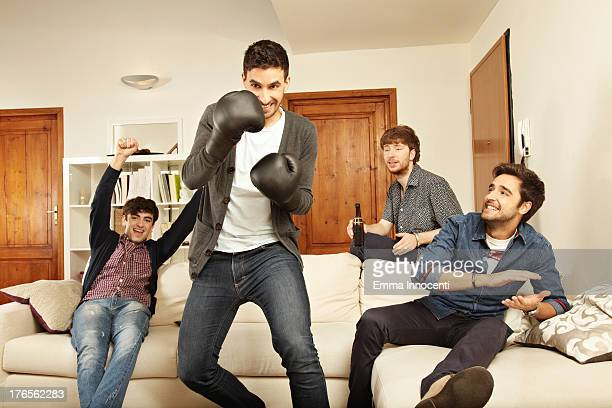 Young men playing boxing with game console