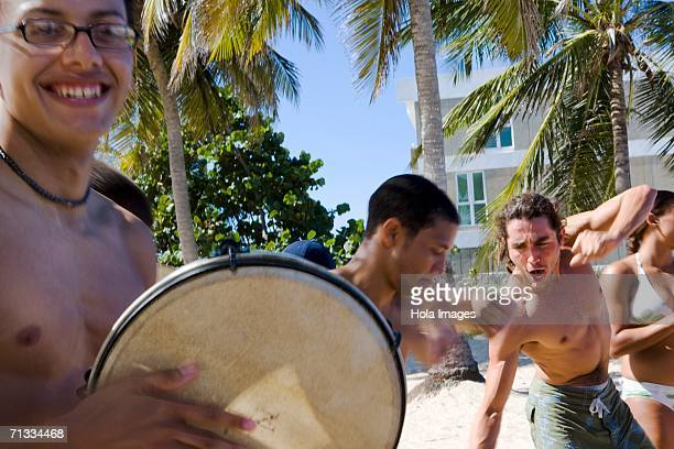 young men playing drums on beach. - dominican ethnicity stock photos and pictures