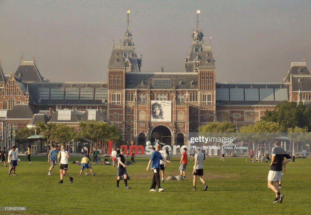Young men playing football in the Museumplein in front of the Rijksmuseum in Amsterdam, Netherlands : Foto de stock