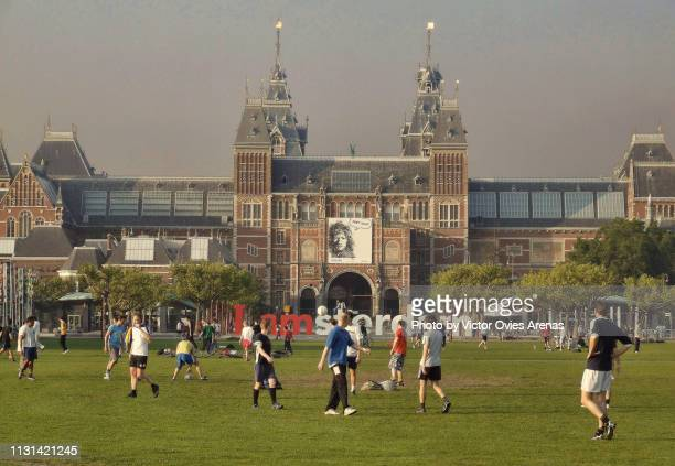 young men playing football in the museumplein in front of the rijksmuseum in amsterdam, netherlands - victor ovies fotografías e imágenes de stock