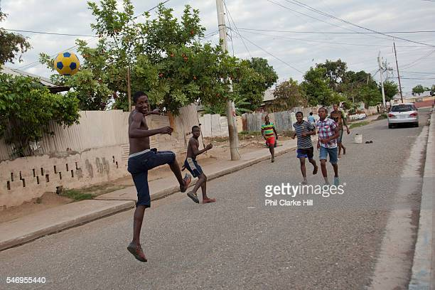 Young men playing football in the street Trenchtown Kingston Jamaica