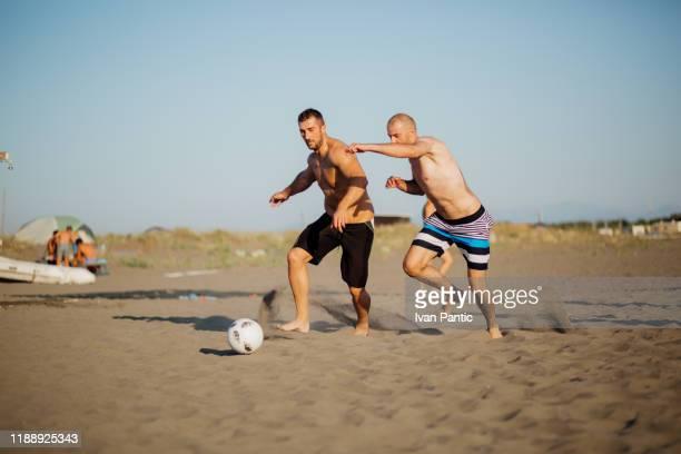 フットボールをする若い男性 - ビーチサッカー ストックフォトと画像