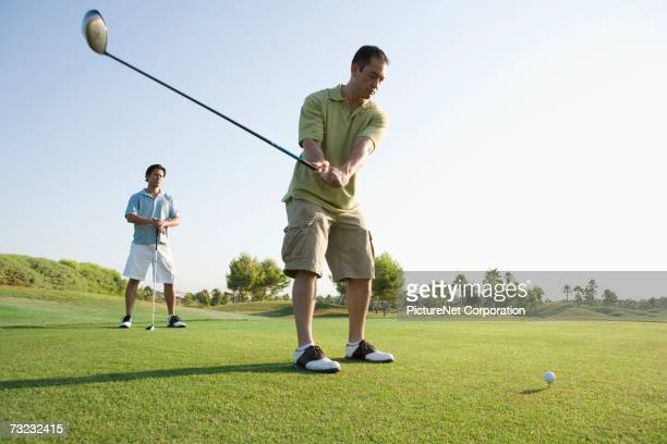 Young men playing golf on golf course