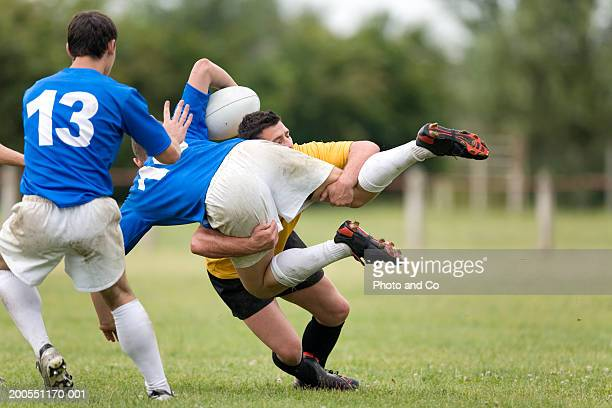 Young men playing rugby, one tackling opponent